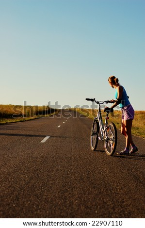 Girl with bicycle on the non-urban road in the sunset.