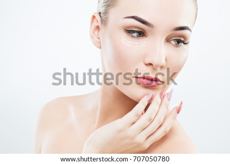 Girl with big green eyes, dark eyebrows, brown hair and naked shoulders holding hands with pink manicure near face, looking aside, light nude make-up.