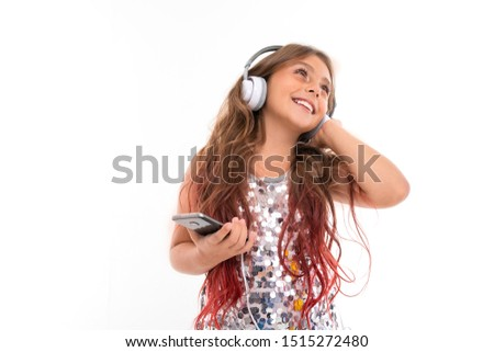 Girl with big white earphones listening to music, touching her left earphone and holding black smartphone isolated