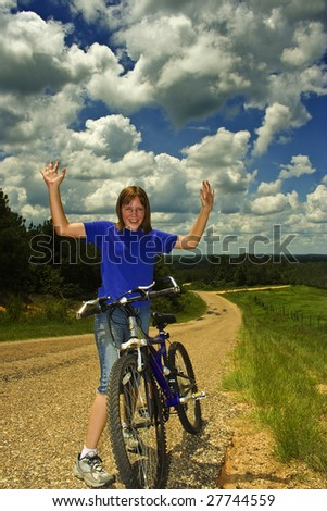 Girl with bike makes it to the top of a hill