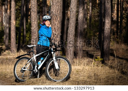 Girl with bike resting in a pine forest