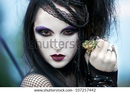 girl with black hair with dark make-up holding a big frog. conceptual photography