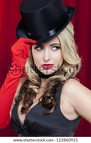 Girl with black hat and red gloves isolated in the red curtain background