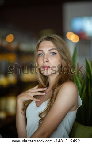 Girl with blue eyes sitting on urban cafe. woman with brown wavy hairstyle.Lifestyle concept. Girl in a cafe with brown hair and in a white dress. Portrait.Bokeh lights, blurred background, greenery #1481519492