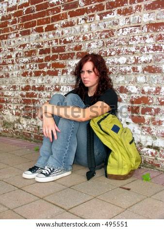 Girl with bookbag sitting against a brick wall