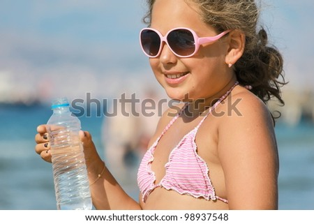 Girl with bottle of water on the beach - stock photo