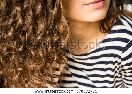 Girl with brown curly hair in a striped T-shirt close-up