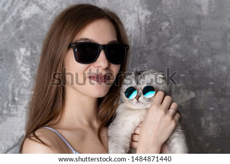 Girl with cat in sunglasses. Like owner like pet concept. Glasses for everybody concept #1484871440