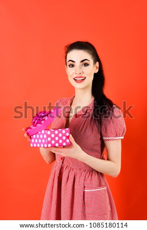 Girl with cheerful face, make up and pink pack. Woman in stylish dress holds present. Lady wears fashionable clothes and smiles. Romance, fashion, style, Womans day, Christmas, shopping concept. #1085180114