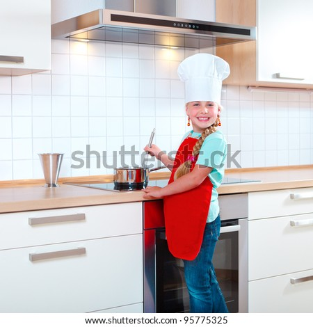 girl with chef's hat cooking in modern kitchen