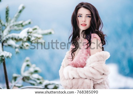 Stock Photo girl with chestnut hair, blue eyes and a pink dress on the background of the winter mountains