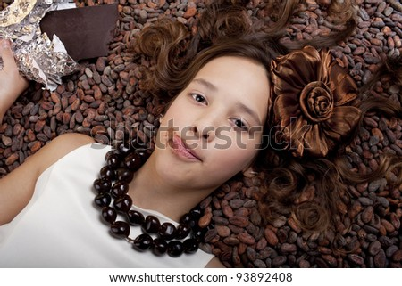girl with chocolate on natural cocoa beans background