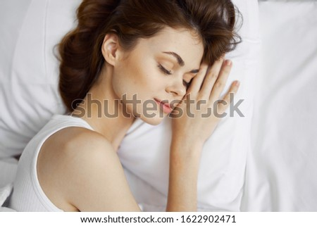girl with closed eyes lies on a pillow charm youth
