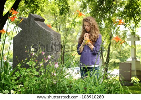 Girl with closed eyes pray in front of a tomb in a cemetery