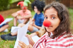 Girl with clown nose practicing for performance on talent show at summer camp