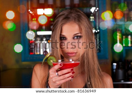 Girl with cocktail on dancing people background