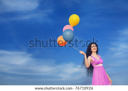 Girl with colorful balloons in the field against the blue sky - stock photo