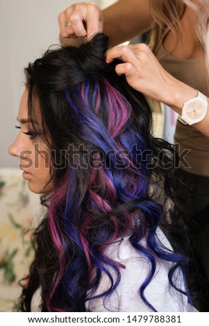 Girl with colorful dyed hair. Model with perfect healthy dyed hair. Side view of attractive brunette woman with stylish hairdo and makeup
