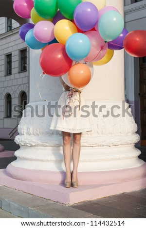 Girl with colorful latex balloons keeping her dress, urban scene, outdoors