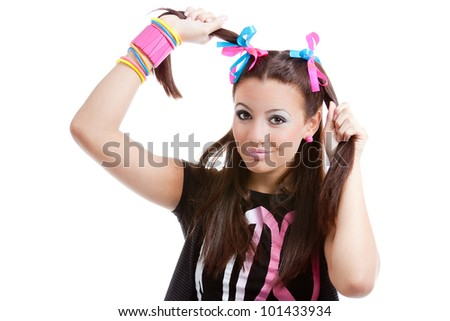 Girl with colorful plaits holds and plays with her hair, isolated on white background. The teenager shows a happy smile and funny expression.