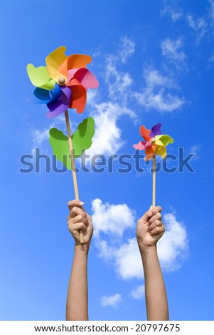 girl with colorful small windmills, concept of wind energy (blue sky)
