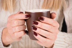 Girl with cup of coffee and brown nails polish. Woman wears beautiful sweater. Manicure and autumn concept. Close up, selective focus