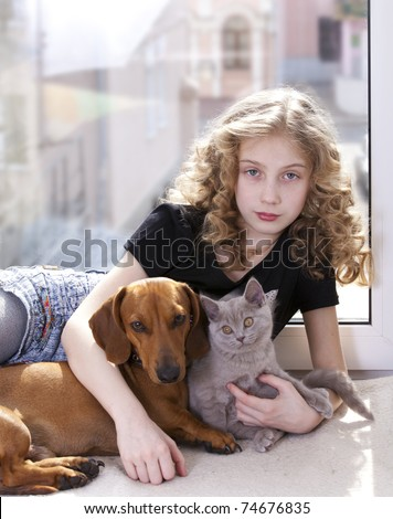 girl with curly hair and a kitten and dog