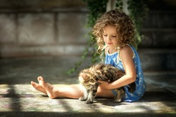 girl with curly hair in a blue sundress played with little fluffy cat in the yard. Retro