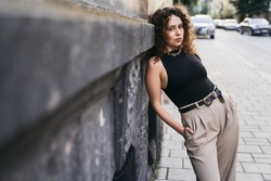 Girl with curly hair. Woman walking down  street. Lady in light pants.