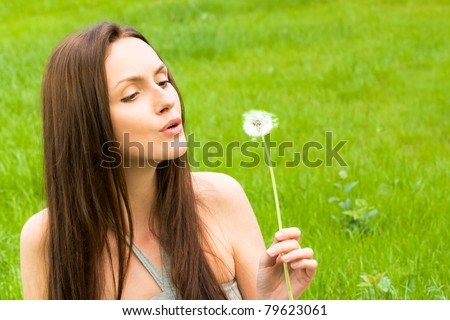 Girl with dandelion on the green field