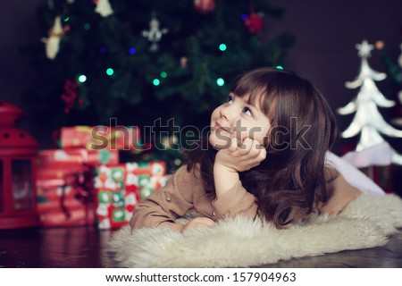 girl with dark hair lying on the carpet. Christmas tree in the background. smiles