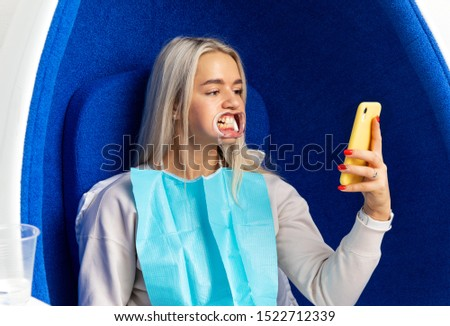 girl with dental caps sitting in a beauty salon for teeth whitening procedure. girl patient makes a selfie on the phone. waiting in the cosmetologist's office #1522712339