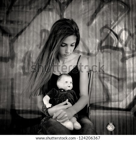Girl with doll. A beautiful teenage girl sitting on a chair holding a doll between her arms.