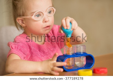 Girl with Down syndrome pours water by means of enema tubes in a test tube