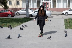 girl with dreadlocks in a black mantle rides on a longboard among pigeons