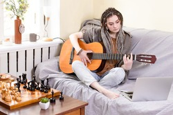 Girl with dreadlocks plays an acoustic guitar while sitting on sofa in front of laptop at home. Concept of inner life, authentic moments, music, hobbies, online guitar learning. Lifestyle. Caucasian.