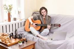 Girl with dreadlocks plays an acoustic guitar while sitting on sofa in front of laptop at home. Concept of inner life, authentic moments, music, hobbies, online guitar learning, lifestyle. Caucasian.