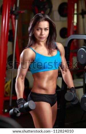 Girl with dumbbells in the gym
