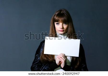 Girl with empty white blank card on a dark wall background
