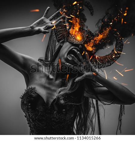 girl with eyes burning with powerful fire and red, wearing a black armor and metal horns, demon