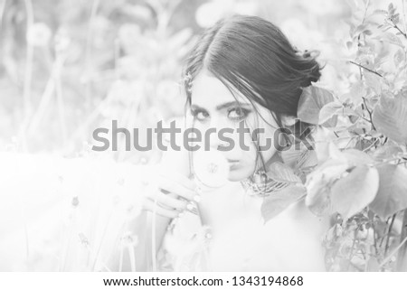 girl with fashionable makeup and beads in green leaves and dandelion flower on natural background, beauty and fashion, youth and freshness #1343194868