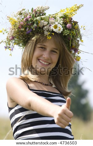 girl with flower wreath showing thumb up. Focus on a face.