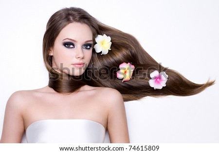 Girl with flowers in her beautiful long straight gloss hair - horizontal