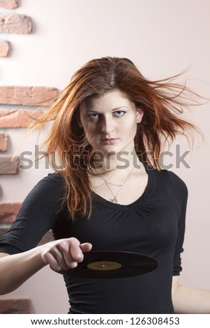 girl with flowing red hair throws vinyl disc