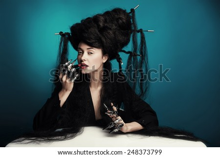 girl with fluffy hair sitting at the table and paints lips