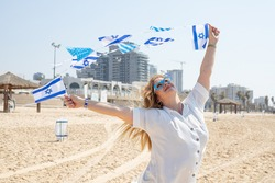 Girl with glasses with the Star of David with a garland of Israel flags on the seashore. Patriotic holiday Independence day Israel - Yom Ha'atzmaut concept.