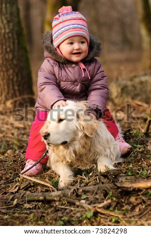 Girl with golden retriever are playing in the park