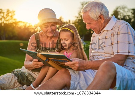 Girl with grandparents, photo album. People looking at photos outdoors. Many years ago.