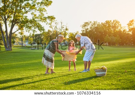 Girl with grandparents, picnic. People in the park, summer. #1076334116