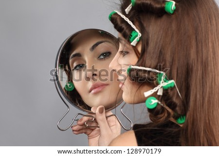 girl with hair curlers looking in the mirror